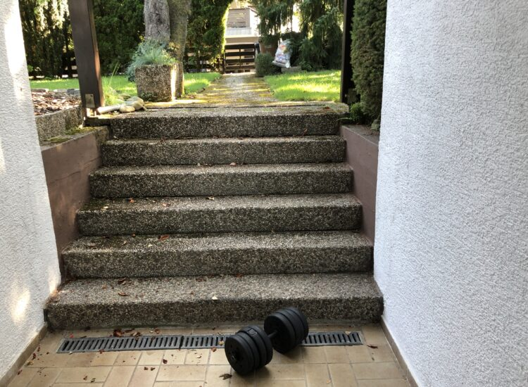 Working out outside, calf raises on the stairs